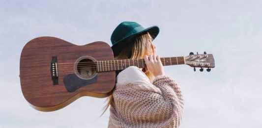 Ragazza con chitarra in spalla che canta canzone d'autore
