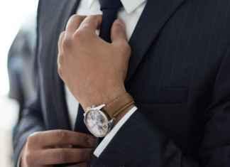 Uomo in abbigliamento da ufficio stringe nodo cravatta