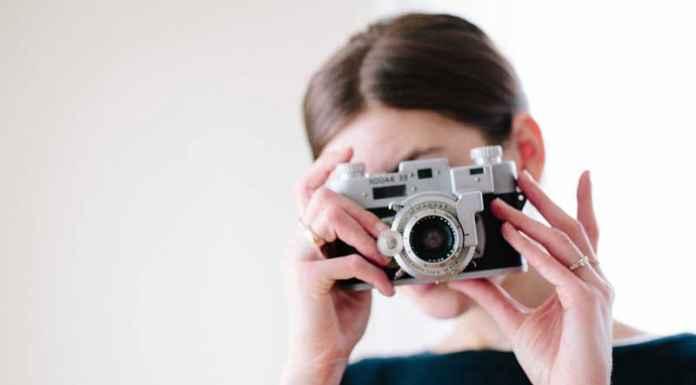 Ragazza con vecchia macchina fotografica a corso fotografia
