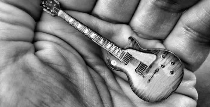 Mano stringe modello di chitarra