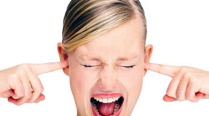 ragazza si tappa le orecchie da suoni sgradevoli