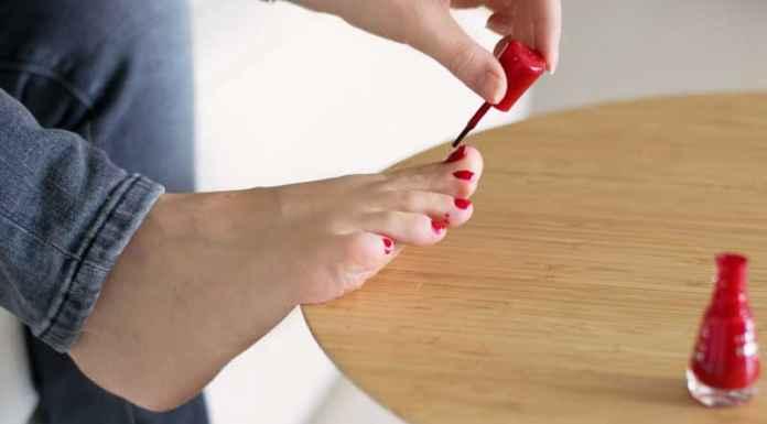 Donna fa la pedicure e si tinge le unghie di rosso