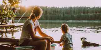 Mamma in vacanza con figli su un lago col cane