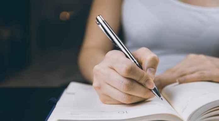 Ragazza intenta a scrivere su un quaderno