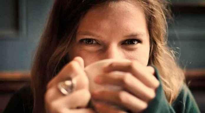 Ragazza di media età felice tazza in mano