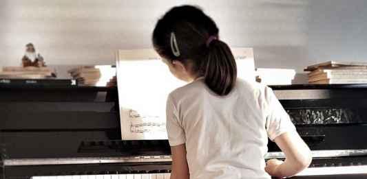 Insegnare musica ad una bambina al piano