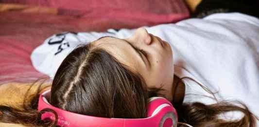 Ragazza con cuffia ascolta musica sdraiata