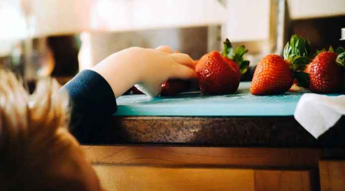 Bambino cerca di prendere fragole